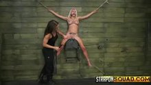 Cute blonde strapped to the wall and fucked by a woman with a strapon
